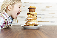 Hungry little girl with stack of baked goods - FSF00860