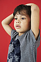 Portrait of little boy with hands on his head in front of red background - FSF00866
