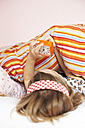 Back view of little girl lying in bed setting the alarm clock - FSF00869