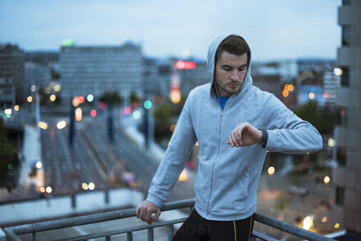 Athlete checking his smartwatch above the city at dawn - DIGF02398 - Daniel Ingold/Westend61