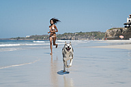 Mexico, Riviera Nayarit beach, young woman running with husky dog - ABAF02150