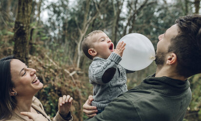 Happy family playing with a balloon in forest - DAPF00727