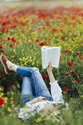 Woman lying in a field reading a book - JPF00190