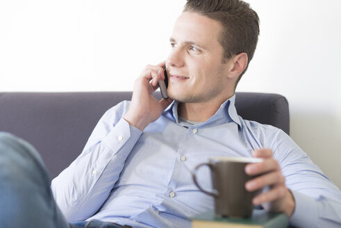 Smiling businessman on couch with smartphone and cup of coffee - FMOF00271