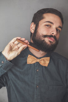 Man combing his beard with a wooden brush, wearing denim shirt and cork bow tie - RTBF00832