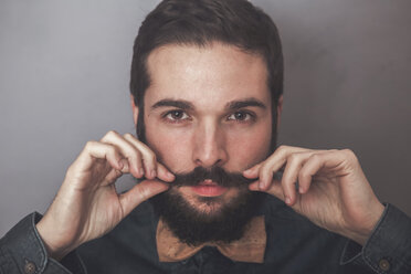 Bearded man adjusting his mustaches, wearing denim shirt and cork bow tie - RTBF00835