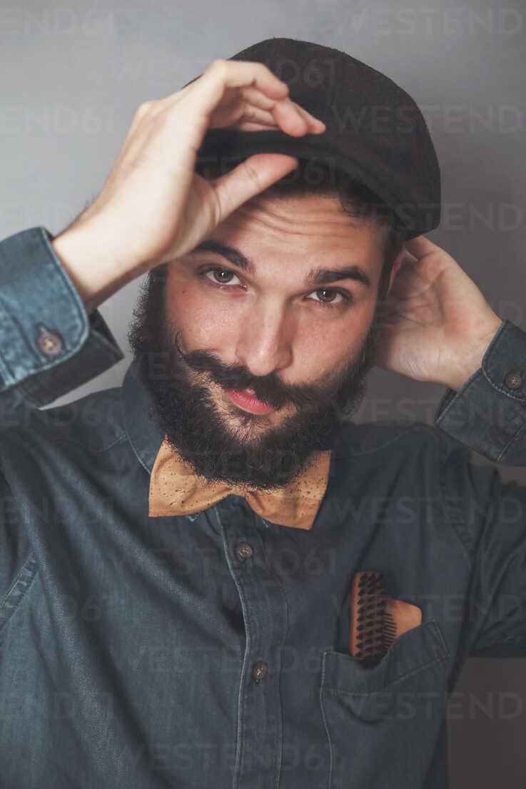 Portrait of bearded man wearing cap, denim shirt, cork bow tie, wearing wooden combs for beard and mustache in his pocket - RTBF00838 - Retales Botijero/Westend61