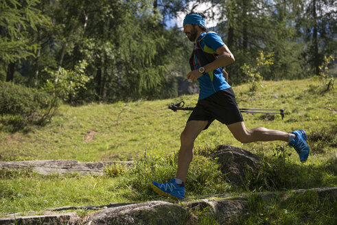 Italy, Alagna, trail runner on the move in forest - ZOCF00260