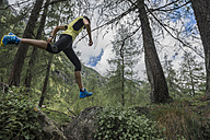 Italy, Alagna, trail runner on the move in forest - ZOCF00266