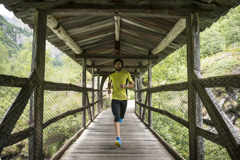 Italy, Alagna, man running on wooden bridge in the mountains - ZOCF00269