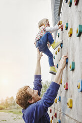 Girl climbing on a wall supported by father - RORF00855
