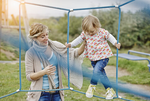 Girl on playground in climbing net supported by mother - RORF00858