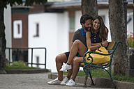 Happy couple sitting on bench in a town - ZOCF00294