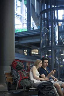 Young couple with backpacks sitting at rail station using smartphone - MVCF00168