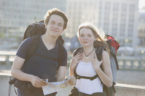 Germany, Berlin, Young couple traveling Berlin with backpacks, looking at map - MVCF00174