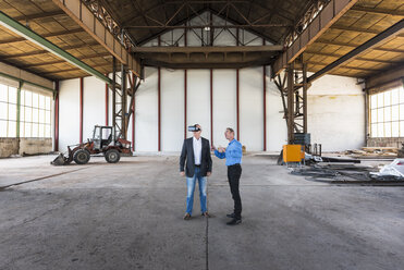 Two businessmen with VR glasses talking in old industrial hall - DIGF02414