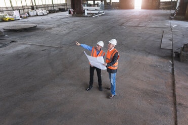 Two men with plan wearing safety vests talking in old industrial hall - DIGF02417