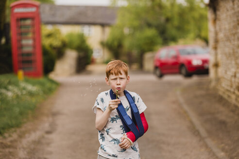 Boy with a broken arm blowing dandelion seeds - NMSF00075
