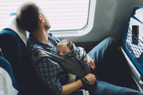 Father on the train holding his sleeping baby in a baby carrier - GEMF01604