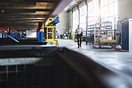 Man walking in industrial hall - DIGF02436