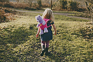 Girl walking with a teddy on her back - NMSF00086