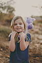 Smiling girl with a teddy outdoors - NMSF00089