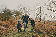 Mother and daughters running on a meadow together - NMSF00092