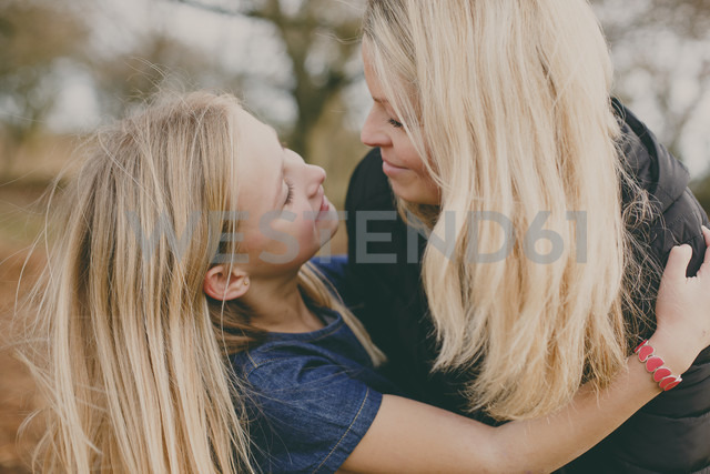 Mother and daughter smiling at each other - NMSF00098