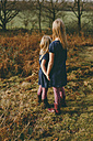 Two sisters standing on a meadow holding hands - NMSF00101