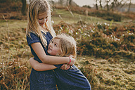Two cute blond sisters cuddling outdoors - NMSF00104