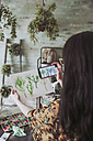Young woman taking pictures of painted plants with her smartphone - RTBF00862