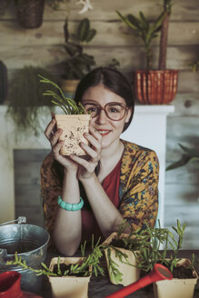 Young woman holding freshly potted cactus - RTBF00880