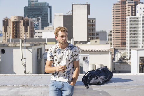 Young man standing on rooftop terrace drinking coffee - WESTF23063