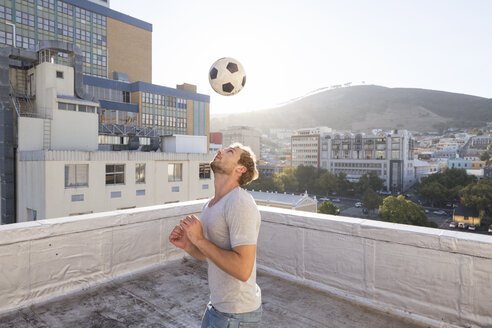 Young man playing football on rooftop terrace - WESTF23069