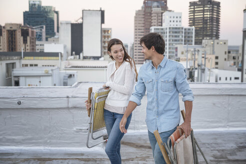 Young couple carrying folding chairs on a rooftop terrace - WESTF23078