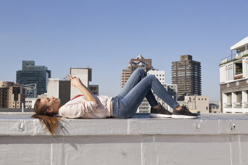 Young woman lying on balustrade of a rooftop terrace, using smart phone - WESTF23081