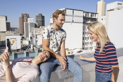 Friends meeting on a rooftop terrace in summer, woman using smartphone - WESTF23084