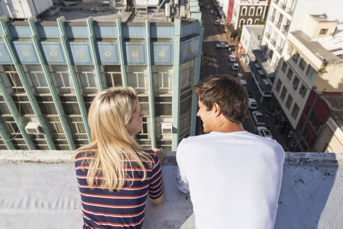 Young couple talking on a rooftop terrace - WESTF23087