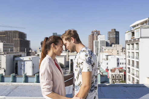 Young couple flirting on a rooftop terrace - WESTF23090