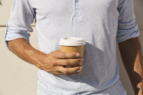 Young man holding cup of take away coffee - WESTF23093