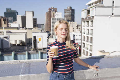 Young woman drinking coffee on a rooftop terrace - WESTF23096