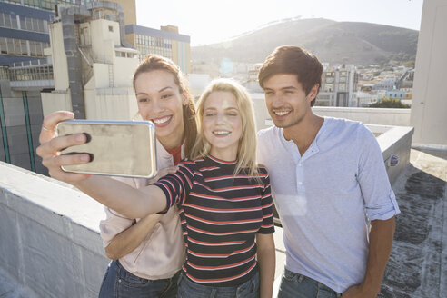 Friends taking selfies on a rooftop terrace - WESTF23099
