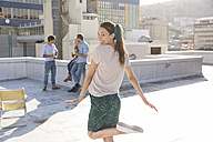 Woman dancing on rooftop terrace with friends in background - WESTF23105
