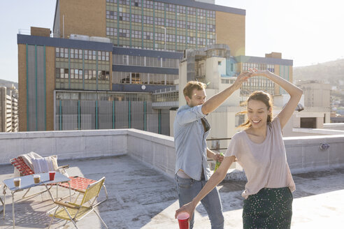 Young couple celebrating on a rooftop terrace, dancing together - WESTF23108