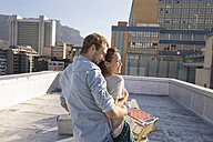 Young couple celebrating on a rooftop terrace, embracing at sunset - WESTF23111