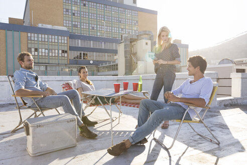 Friends having a rooftop party on a beautiful summer evening - WESTF23114