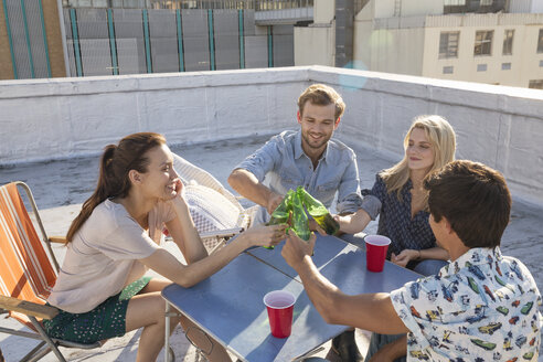 Friends having a rooftop party on a beautiful summer evening - WESTF23117