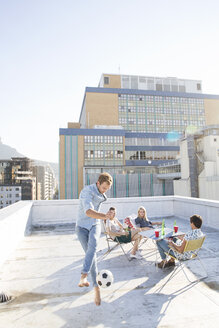 Friends meeting on rooftop terrace in summer, playing football - WESTF23120