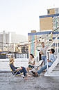 Friends having a rooftop party on a beautiful summer evening - WESTF23135