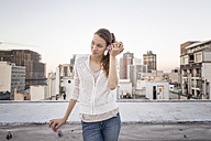 Young woman standing on a rooftop terrace, using smartphone - WESTF23147
